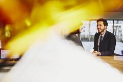 Business man and woman having a conversation in an office. Primary colors: yellow and white.
