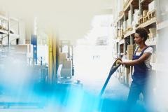 Female African-American worker operating a pallet loader in a logistics environment. Serious facial expression. Primary color blue. Secondary color white.