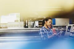 Female Asian factory worker operating a touch-screen display. Hair in a ponytail. Checkered shirt. Primary color blue.